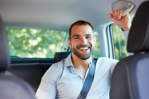 Cheerful businessman sitting in a car
